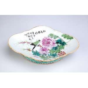 Covilhete de porcelana policromada e dourada,<br>ovalada e recortada, decoração com pássaro e flores.<br />24 x 16 cm. Japão, séc. XIX.