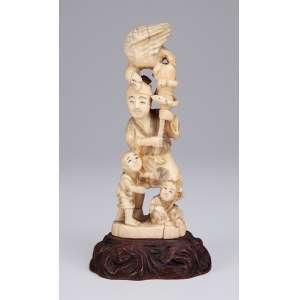 Escultura de marfim. Figura masculina com crianças, ave e serpente. <br />Sobre base de madeira lavrada. 18,5 cm de altura.