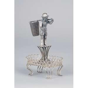 Paliteiro de prata, lavrador com balaio em seu costado, sobre base avarandada. <br />13,5 cm de altura. Brasil, séc. XIX.