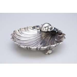Concha de prata repuxada, sobre três pés em caramujos. 22 x 21 cm. Marca do teor 833, <br />demais contrastes não identificados. Europa, séc. XIX.