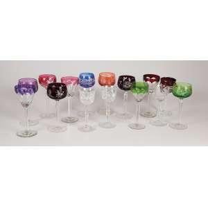 Coleção de 15 taças de cristal, sendo 12 coloridas de diferentes lapidação e três translúcidas iguais. <br />19,5 cm de altura, o maior. Bohemia, séc. XX.