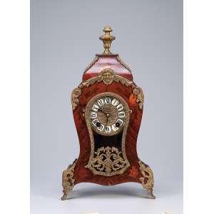 Relógio de mesa estilo Louis XV, caixa de madeira com marchetaria floral, ornamentos de bronze. <br />Mostrador circular com números romanos sobre placas esmaltadas. <br />20 x 10 x 39 cm de altura. França, séc. XX.