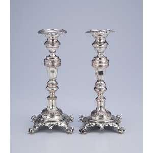 Dois castiçais de prata, muito semelhantes. Fuste fuso, base quadrangular e pés em garra. <br />22,5 cm de altura. Contraste do Porto, meados do séc. XIX.