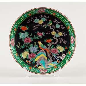 Medalhão de porcelana policromada, caldeira decorada com pássaros e flores sobre fundo preto. <br />40,5 cm de diâmetro. China, séc. XIX.