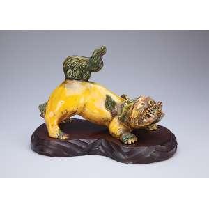 Leão de fó moldado em porcelana em tons de amarelo, marrom e verde. <br />Base de madeira. 27 x 16 x 20 cm de altura. China, séc. XIX.