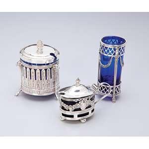 Conjunto de três porta-condimentos de prata repuxada e cinzelada, internamente em vidro azul cobalto. <br />10 cm de altura, o maior. Inglaterra e França, séc. XX.