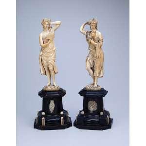 Finas esculturas de marfim, pendant de figuras femininas ao estilo néo clássico. <br />Apresentam-se sobre base pedestal de madeira com incrustações de marfim. <br />42 cm de altura. França, séc. XIX.