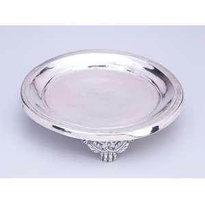 Salva de prata repuxada e cinzelada, circular, sobre três pés em garra. <br />17 cm de diâmetro. Sem contrastes. Séc. XIX.