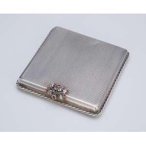 Porta-pó de prata guilhochada, fecho com pequenos rubis incrustados. <br />8 X 8 cm Itália, séc. XX.