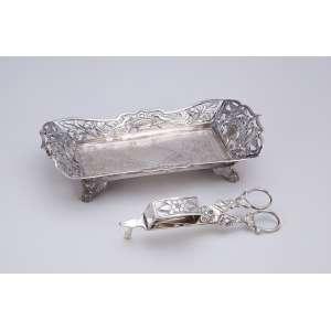 Tesoura espevitadeira (no estado) e bandeja de prata repuxada e cinzelada. A bandeja com contraste <br />para Lisboa e a tesoura com contraste 10 dinheiros. 21,5 x 10,5 cm, a bandeja. Séc. XIX.