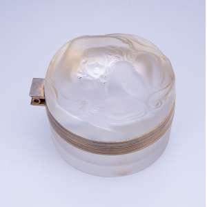 LALIQUE<br />Caixa circular com tampa basculante de vidro pressé moulé. Na tampa figura feminina. <br />8 cm de diâmetro x 5 cm de altura. Assinada. França, c. 1950.