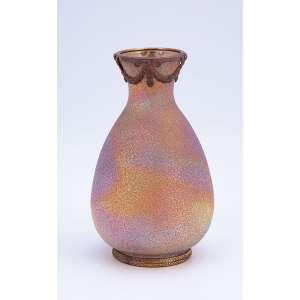 Pequeno vaso de vidro iridiscente. Base e bocal com ornamentos de metal prateado. <br />13,5 cm de altura. França, séc. XX.