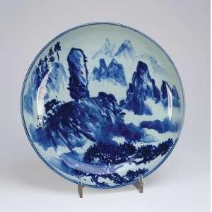 Grande medalhão de porcelana azul e branca, caldeira decorada com paisagem montanhosa. <br />40 cm de diâmetro. Japão, séc. XX.