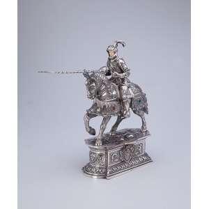 Guerreira sobre cavalo, ambos com indumentária de combate. Escultura em prata e marfim com incrustações <br />de pedras (algumas faltas), sobre base pedestal. 20 x 10 x 30 cm de altura. Espanha, séc. XX.