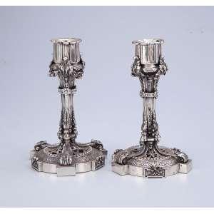 Par de pequenos castiçais de prata francesa, base circular, fenestrada, fuste e bobéche <br />com guirlandas. 15,5 cm de altura. Contraste cabeça de Mercúrio indicando o teor 950 em <br />uso a partir de 1879.