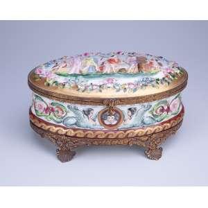 Caixa de porcelana ovalada, decorada com personagens e flores ao gosto das peças Capodimonte. <br />Base e moldura da tampa em metal dourado. 25 x 16 x 13 cm de altura. Itália, séc. XX.