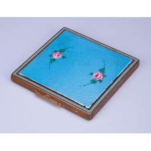 Caixa toucador de metal guilhochado e dourado. Tampa revestida de esmalte azul <br />celeste com rosas. 7,5 x 7,5 cm. U.S.A. séc. XX.