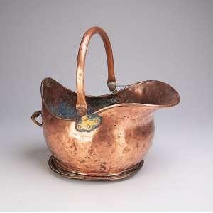 Utensílio de cobre para lareira, usado para guarda de nó de pinho, alça retrátil. <br />38 x 27 x 23 cm de altura. Brasil, séc. XIX.