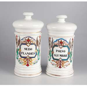 Par de potes de farmácia de porcelana francesa, branca, decorados em policromia. 24 cm de altura cada. <br />Ambos com indicação do conteúdo: POLVO ALUMBRE e SEBO FLANDES. França, séc. XIX.