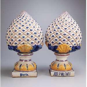 Par de pinhas de louça branca, vidrada, formato de abacaxi, tons de azul e amarelo. <br />55 cm de altura. Na base a inscrição. JOSE P. VALENTE - Porto. Portugal, séc. XIX.