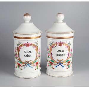Par de potes de farmácia de porcelana policromada e dourada, ambos com indicação de conteúdo: <br />AZUCAR CRIST: e JABON MEDICIN. 29 cm de altura. França, séc. XIX.