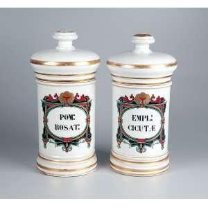 Par de potes de farmácia de porcelana branca com policromia e douração, reservas com indicação do conteúdo <br />POM ROSAT e EMPL CICUTAE. 27 cm de altura. França, séc. XIX.