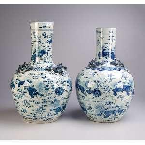 Dois potiches de porcelana chinesa azul e branca, decorados com dragões em relevo. <br />57 cm x 53 de altura. China, séc. XIX.