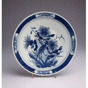 Medalhão de porcelana japonesa azul e branca, ao estilo dos Ming, circular com barrado na orla e plano ornamentado com ramos florais e pássaro. 40,5 cm de diâmetro. Séc. XIX.