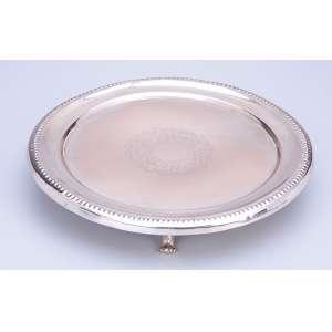 Salva de prata repuxada, circular, borda perolada e plano com rosácea burilada; <br />sobre três pés. 20 cm de diâmetro.