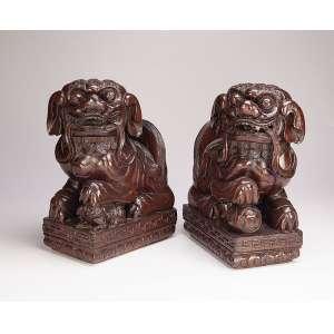 Pendant de esculturas de madeira entalhada e polida, casal de quimeras, o macho com a pata sobre a <br />esfera representando o mundo, a fêmea com sua cria. 40 cm de altura cada. China, séc. XIX.