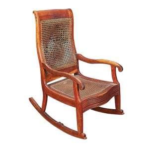 Antiga cadeira de balanço de madeira lavrada, assento e encosto de palhinha e parte frontal em caneluras.<br />107 cm de altura, o espaldar. Brasil, séc. XIX. (necessita restauro no encosto).