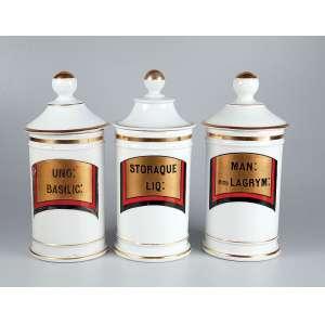 Conjunto de três potes de farmácia de porcelana branca e dourada, todos com indicação de conteúdo.<br />MAN em LAGRYM, SOTORAQUE, LIQ e UNG BRASILIC. (um com fio de cabelo).
