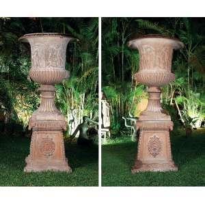 Par de monumentais e antigos vasos de ferro fundido, estilo Medici, apoiados sobre coluna pedestal. Bojo dos vasos decorados com figuras em cenas neoclássicas caneluras e cariátides. As colunas ornadas por cabeças de caprino. - 165 cm somente o vaso. 110 cm a base; altura total 275 cm.