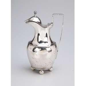 Pequena jarra com tampa basculante, de prata repuxada, bojo com barrado de gregas, sobre quatro <br />pés em esfera.18,5 cm de altura. Contraste de Lisboa datável para 1a. metade do séc. XIX.