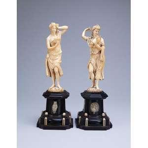 Finas esculturas de marfim, pendant de figuras femininas ao estilo néo-clássico. Base pedestal <br />de madeira com incrustações de marfim. 42 cm de altura. França, séc. XIX.