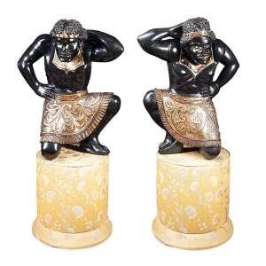 Dois blackmoours de madeira ebanizada. - Apresentam-se ajoelhados, com saiote dourado. Base pedestal. - 83 cm de altura; 155 cm de altura total. - Itália, séc. XVIII.