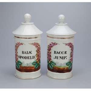 Par de potes de farmácia de porcelana branca e dourada, decorados com paisagem e flores. Ambos com <br />indicação do conteúdo. 28 cm de altura. França, séc. XIX. (um deles com mínimo bicado e trinco).
