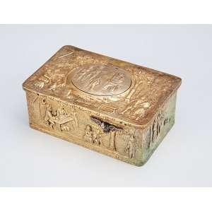 Caixa retangular de bronze dourado, com mecanismo musical de corda. Decoração com relevo, retratando cenas do cotidiano. - 10 x 7 x 4,5 cm. - Europa, séc. XIX.