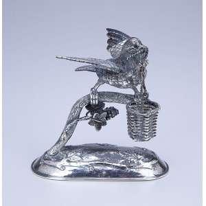 Paliteiro de prata repuxada e cinzelada, pomba carregando cesto no bico. - 11 cm de altura. - Marca do teor 925 e da prataria S.P. - Brasil, séc. XX.