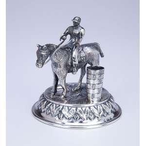 Paliteiro de prata, repuxada e cinzelada. Cavalo com Jockey ao lado de cesto. <br />12 cm de altura. Marca do teor 925. Europa, séc. XIX.