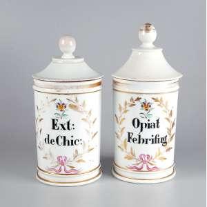 Dois potes de farmácia de porcelana branca e dourada, ambos com indicação do conteúdo: EXT DE CHIC e OPIAL FEBRIFUG. - 27 cm de altura, o maior. - França, séc. XIX.