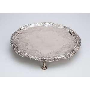 Salva circular de prata repuxada e cinzelada, decoração barroca com conchas e volutas; <br />sobre quatro pés em sapata. 26 cm de diâmetro. Contraste para Lisboa e marca do <br />prateiro Dionísio Gomes da Silva citado entre 1758 - 1759.