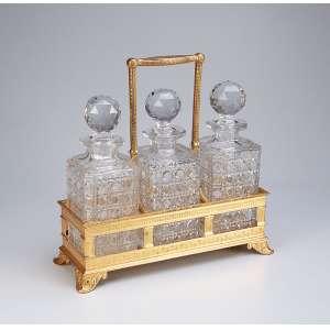 Tantalus com três garrafas de cristal de Baccarat em finíssimo suporte de bronze cinzelado e <br />dourado a ouro com chancela inglesa da fábrica Elkington & Co. Europa, séc. XIX.