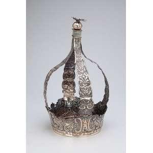 Grande coroa de prata repuxada e cinzelada, quatro hastes encimadas por esfera e o Divino. <br />15 cm de diâmetro x 34 cm de altura. Brasil, séc. XIX.