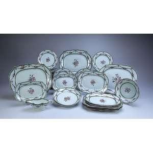 Remanescente de aparelho de jantar de porcelana Cia das Índias, composto de 10 travessas retangulares de diversos tamanhos (40 x 29 cm, as maiores), três travessas fundas circulares e uma molheira, 26 pratos rasos e 28 fundos, totalizando 68 peças. Decoração em guirlandas florais na aba, buquê de flores no plano. - China, Qing Qianlong - (1736-1795).