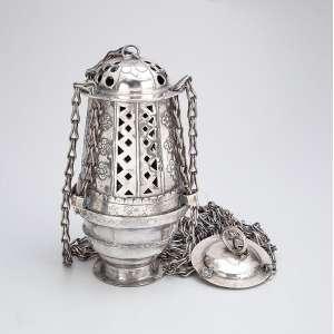 Turíbulo de prata com suas correntes suspensórias. Apresenta inscrições e a data de 1898. 2 - 2 cm de altura (o turíbulo) e 102 cm de altura total. - América espanhola, séc. XIX.