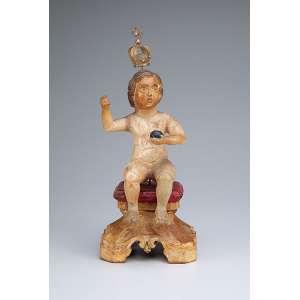 Menino Jesus. - Escultura de madeira patinada. Apresenta-se sentado sobre almofada. Coroa de filigrana dourada. - 30 cm de altura total. - Brasil, séc. XIX.