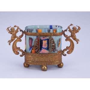Pequeno floreiro de pasta de vidro ornamentado por dois anjos a guisa de alças e demais ornamentos em metal dourado. - 12,5 x 7,5 cm. - Europa, séc. XX.