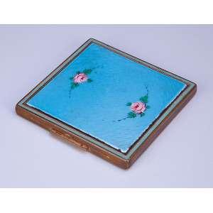 Caixa toucador de metal guilhochado e dourado. Tampa revestida de esmalte azul celeste com rosas. - 7,5 x 7,5 cm. - U.S.A. séc. XX.