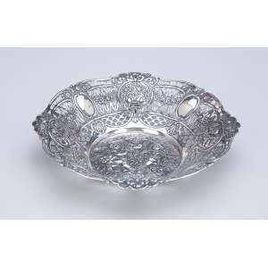 Pequeno centro de mesa de prata repuxada e cinzelada, circular, borda fenestrada e plano com três <br />anjos entre flores. 21,5 cm de diâmetro. Marca do teor 800. Séc. XX.<br />Base: de 500 por 400